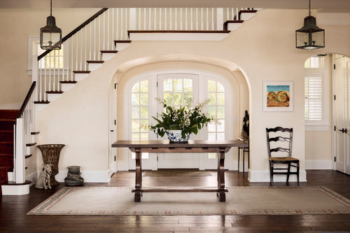 A Classic Wood Staircase Frames The Glass Paneled Arched Doorway That  Streams Southern Light Throughout.
