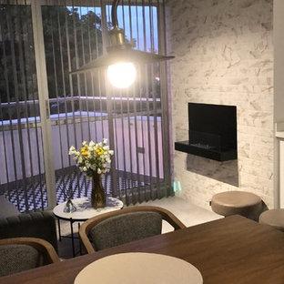 Aménagement d'une salle à manger éclectique avec cheminée suspendue et un manteau de cheminée en brique.