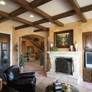 Ejemplo de sala de estar cerrada, mediterránea, de tamaño medio, con paredes amarillas, suelo de baldosas de terracota, chimenea tradicional, marco de chimenea de piedra, pared multimedia y suelo naranja
