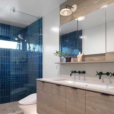Example of a large trendy master beige floor and double-sink alcove shower design in Hawaii with flat-panel cabinets, light wood cabinets, white walls, a floating vanity, a wall-mount sink, quartz countertops, a hinged shower door and beige countertops