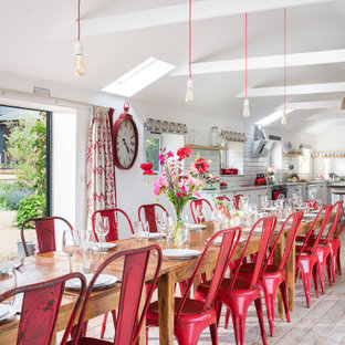 This is an example of a large country open plan dining room in Cornwall with white walls and painted wood flooring.
