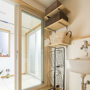 Example of a danish beige floor dedicated laundry room design in Other with white cabinets and white walls