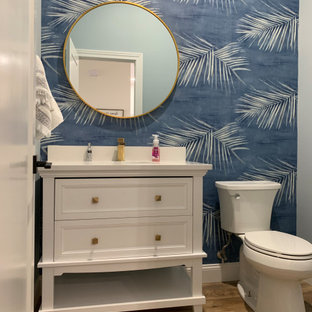 This is an example of a large transitional 3/4 bathroom in Other with recessed-panel cabinets, white cabinets, a one-piece toilet, blue walls, vinyl floors, an undermount sink, engineered quartz benchtops, brown floor, white benchtops, a single vanity, a built-in vanity and wallpaper.