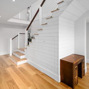 Modelo de escalera en L y machihembrado, de estilo de casa de campo, con escalones de madera, barandilla de cable y machihembrado