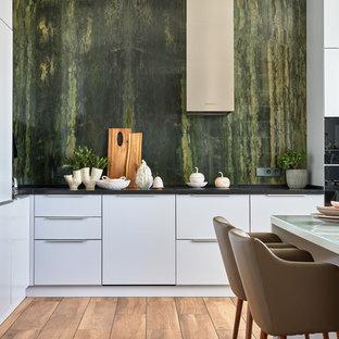 Идея дизайна: угловая кухня в современном стиле с обеденным столом, плоскими фасадами, белыми фасадами, зеленым фартуком, фартуком из каменной плиты, коричневым полом и черной столешницей без острова
