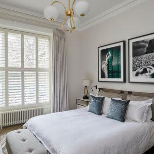 ロンドンの広いトランジショナルスタイルのおしゃれな主寝室 (白い壁、淡色無垢フローリング、グレーの床、格子天井、暖炉なし) のインテリア