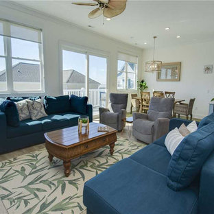 ローリーの大きいビーチスタイルのおしゃれなLDK (白い壁、ラミネートの床、壁掛け型テレビ、ベージュの床) の写真