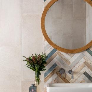 Пример оригинального дизайна: ванная комната среднего размера в стиле кантри с фасадами с филенкой типа жалюзи, светлыми деревянными фасадами, разноцветной плиткой, керамогранитной плиткой, разноцветными стенами, полом из керамогранита, душевой кабиной, накладной раковиной, столешницей из дерева, белым полом, бежевой столешницей, фартуком, тумбой под одну раковину, напольной тумбой и балками на потолке