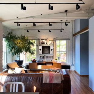 Mittelgroßes, Offenes Modernes Wohnzimmer mit braunem Holzboden, Wand-TV, freigelegten Dachbalken und Ziegelwänden in Boston