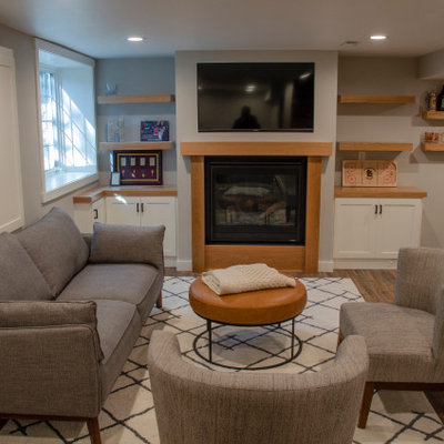 Mid-sized elegant underground vinyl floor and brown floor basement photo in Minneapolis with a bar, gray walls, a standard fireplace and a wood fireplace surround