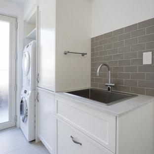 Idéer för att renovera en mellanstor vintage vita parallell vitt tvättstuga enbart för tvätt, med en nedsänkt diskho, skåp i shakerstil, vita skåp, bänkskiva i kvarts, beige stänkskydd, stänkskydd i keramik, vita väggar, klinkergolv i porslin, en tvättmaskin och torktumlare bredvid varandra och beiget golv