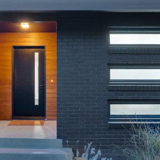 Diseño de puerta principal madera, retro, grande, con paredes marrones, suelo de cemento, puerta simple, puerta negra, suelo gris y madera
