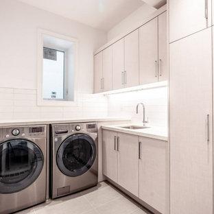 Exempel på ett mellanstort modernt vit l-format vitt grovkök, med en nedsänkt diskho, släta luckor, skåp i ljust trä, bänkskiva i kvarts, vitt stänkskydd, stänkskydd i glaskakel, vita väggar, klinkergolv i keramik, en tvättmaskin och torktumlare bredvid varandra och grått golv