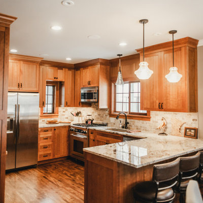 Inspiration for a mid-sized craftsman u-shaped dark wood floor and brown floor eat-in kitchen remodel in Minneapolis with an undermount sink, recessed-panel cabinets, medium tone wood cabinets, granite countertops, beige backsplash, stone tile backsplash, stainless steel appliances, a peninsula and beige countertops