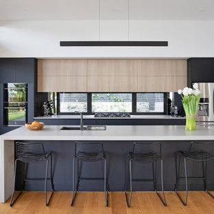 Design ideas for a beach style kitchen in Sunshine Coast with an undermount sink, flat-panel cabinets, black cabinets, window splashback, stainless steel appliances, medium hardwood floors, with island and white benchtop.
