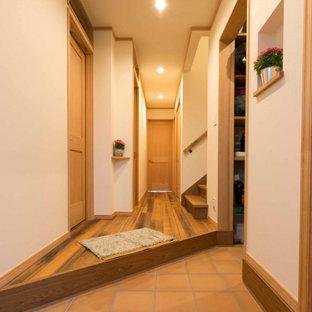横浜の広いラスティックスタイルのおしゃれな玄関ホール (濃色無垢フローリング、茶色い床、クロスの天井、ベージュの天井) の写真