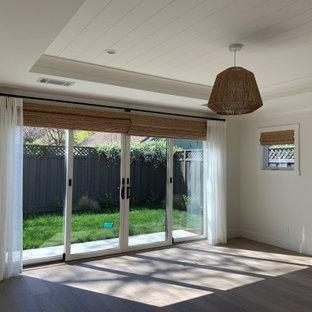 Mittelgroßes Country Hauptschlafzimmer mit weißer Wandfarbe, hellem Holzboden, grauem Boden, Kassettendecke und Holzdielenwänden in San Francisco