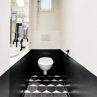 Идея дизайна: туалет среднего размера в современном стиле с плоскими фасадами, черными фасадами, инсталляцией, белой плиткой, зеркальной плиткой, белыми стенами, полом из цементной плитки, настольной раковиной, столешницей из кварцита, черным полом и белой столешницей