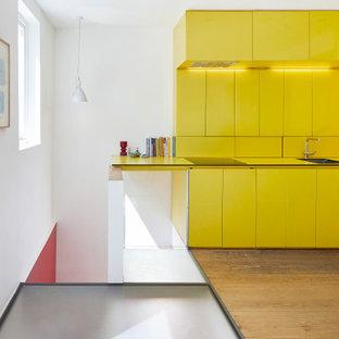 Идея дизайна: маленькая прямая кухня-гостиная в современном стиле с накладной раковиной, плоскими фасадами, желтыми фасадами, столешницей из ламината, желтым фартуком, светлым паркетным полом и желтой столешницей без острова