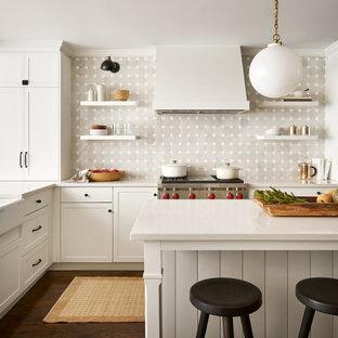 Идея дизайна: угловая кухня среднего размера в стиле кантри с раковиной в стиле кантри, фасадами в стиле шейкер, белыми фасадами, столешницей из кварцевого агломерата, разноцветным фартуком, фартуком из терракотовой плитки, техникой из нержавеющей стали, паркетным полом среднего тона, двумя и более островами, коричневым полом и белой столешницей