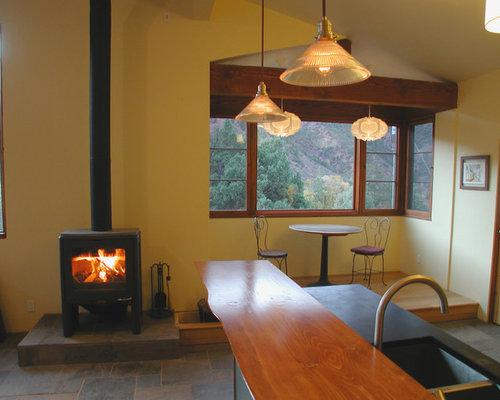 Sala da pranzo aperta verso la cucina con stufa a legna e pareti ...