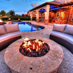 Immagine di un grande patio o portico classico dietro casa con un focolare, graniglia di granito e un tetto a sbalzo