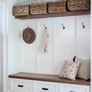 Diseño de puerta principal boiserie, de estilo de casa de campo, pequeña, con paredes blancas, suelo de madera oscura, puerta simple, puerta de madera en tonos medios, suelo marrón y boiserie