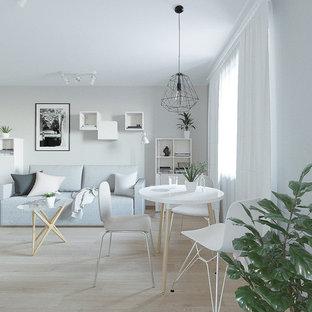 Ejemplo de salón abierto, nórdico, pequeño, con paredes grises, televisor colgado en la pared, suelo laminado y suelo rosa