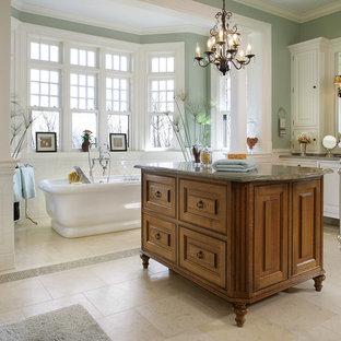 Идея дизайна: большая главная ванная комната в классическом стиле с фасадами островного типа, фасадами цвета дерева среднего тона, отдельно стоящей ванной, душевой комнатой, раздельным унитазом, зеленой плиткой, зелеными стенами, полом из известняка, врезной раковиной, столешницей из гранита, желтым полом, душем с распашными дверями и зеленой столешницей