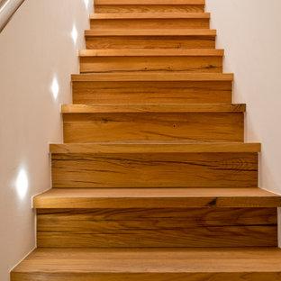 Idée de décoration pour un escalier droit chalet de taille moyenne avec des marches en bois, des contremarches en bois, un garde-corps en métal et un mur en parement de brique.
