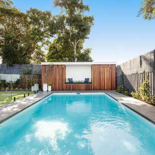 Photo of a large contemporary backyard rectangular pool in Melbourne with a pool house and natural stone pavers.