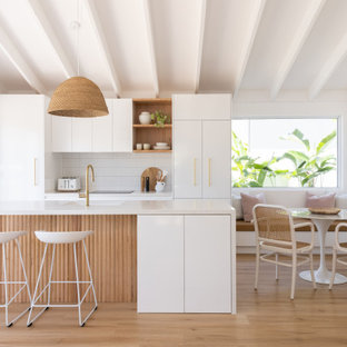 This is an example of a beach style galley open plan kitchen in Sydney with white splashback, ceramic splashback, an undermount sink, flat-panel cabinets, white cabinets, panelled appliances, medium hardwood floors, with island, brown floor, white benchtop, exposed beam and vaulted.