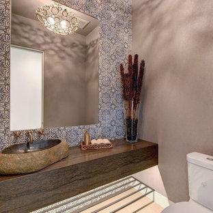 他の地域の中くらいのエクレクティックスタイルのおしゃれなトイレ・洗面所 (茶色いキャビネット、分離型トイレ、青いタイル、テラコッタタイル、グレーの壁、磁器タイルの床、ベッセル式洗面器、ライムストーンの洗面台、グレーの床、ブラウンの洗面カウンター、フローティング洗面台、クロスの天井、壁紙) の写真