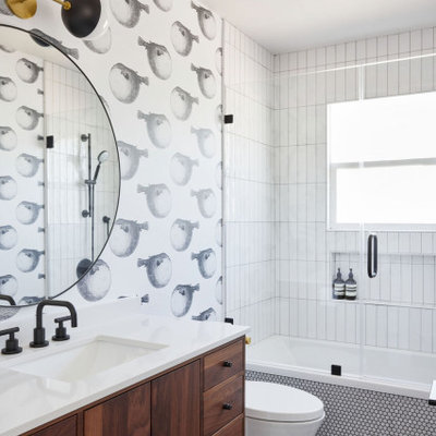 Example of a mid-sized mid-century modern kids' white tile and ceramic tile porcelain tile, gray floor, single-sink and wallpaper drop-in bathtub design in San Francisco with flat-panel cabinets, brown cabinets, a one-piece toilet, a drop-in sink, quartz countertops, a hinged shower door, white countertops and a freestanding vanity