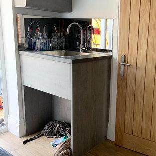 Idéer för att renovera en liten tvättstuga, med en enkel diskho, släta luckor och spegel som stänkskydd
