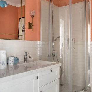 Idee per una piccola stanza da bagno con doccia boho chic con ante con bugna sagomata, ante bianche, doccia ad angolo, WC sospeso, piastrelle arancioni, piastrelle in ceramica, pareti arancioni, pavimento con piastrelle in ceramica, lavabo integrato, top in superficie solida, pavimento grigio, porta doccia scorrevole e top beige