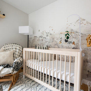 Small eclectic gender-neutral light wood floor and wallpaper nursery photo in Denver with beige walls