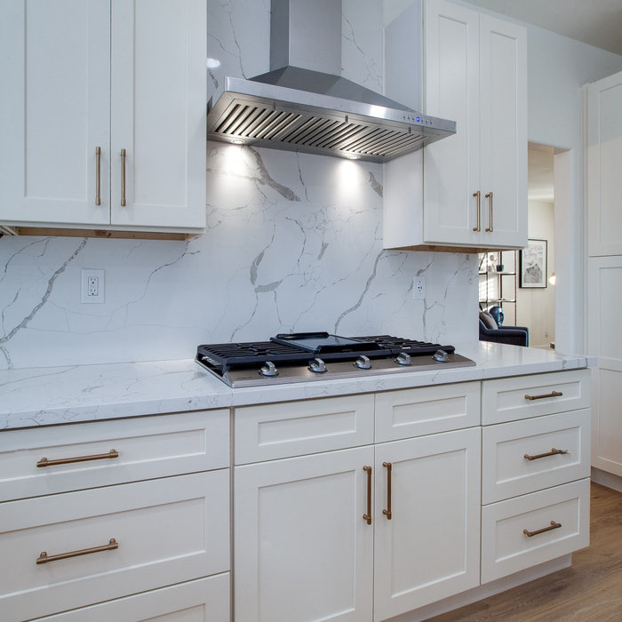This kitchen was transformed from an 80's brown and black theme to a light and bright white kitchen. Featured waterfall island. New cabinetry with brass hardware, a farmhouse sink with sparking new st