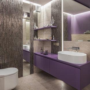 Свежая идея для дизайна: главная ванная комната среднего размера в современном стиле с плоскими фасадами, фиолетовыми фасадами, угловым душем, инсталляцией, бежевой плиткой, керамогранитной плиткой, фиолетовыми стенами, полом из керамогранита, накладной раковиной, стеклянной столешницей, бежевым полом, душем с распашными дверями, фиолетовой столешницей, подвесной тумбой, потолком с обоями и обоями на стенах - отличное фото интерьера