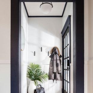 Imagen de distribuidor clásico renovado, pequeño, con paredes blancas, suelo de madera en tonos medios, puerta simple, puerta negra y suelo marrón