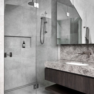 This is an example of a mid-sized contemporary master bathroom in Melbourne with furniture-like cabinets, dark wood cabinets, a freestanding tub, an alcove shower, a one-piece toilet, gray tile, ceramic tile, grey walls, ceramic floors, an undermount sink, limestone benchtops, grey floor, a hinged shower door, grey benchtops, a niche, a double vanity and a built-in vanity.