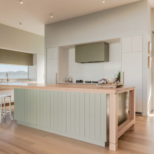 Inspiration for a large contemporary u-shaped kitchen pantry in Sunshine Coast with a farmhouse sink, shaker cabinets, green cabinets, laminate benchtops, white splashback, black appliances, laminate floors, with island, beige floor and beige benchtop.