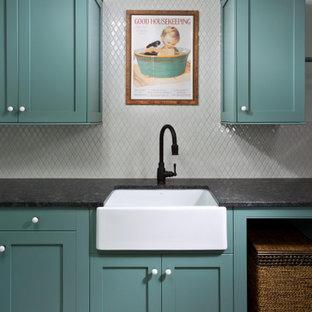 Inredning av en klassisk stor svarta svart tvättstuga enbart för tvätt, med en rustik diskho, skåp i shakerstil, turkosa skåp, granitbänkskiva, vitt stänkskydd, stänkskydd i keramik, vita väggar, klinkergolv i keramik, en tvättpelare och flerfärgat golv