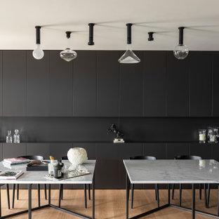 Идея дизайна: гостиная-столовая в стиле модернизм с серыми стенами, светлым паркетным полом, многоуровневым потолком и панелями на стенах