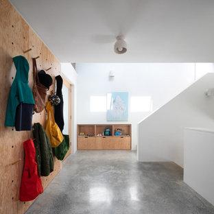 Свежая идея для дизайна: фойе в современном стиле с белыми стенами, бетонным полом, одностворчатой входной дверью, стеклянной входной дверью и серым полом - отличное фото интерьера