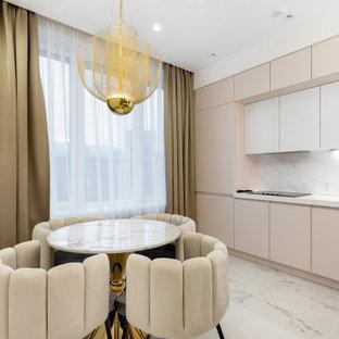 На фото: прямая кухня в современном стиле с обеденным столом, плоскими фасадами, розовыми фасадами, белым фартуком и белым полом с