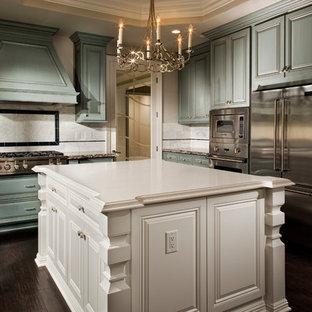 Foto på ett stort vintage kök, med en undermonterad diskho, luckor med upphöjd panel, blå skåp, bänkskiva i kvarts, vitt stänkskydd, stänkskydd i stenkakel, rostfria vitvaror, mörkt trägolv, en köksö och brunt golv
