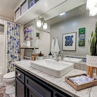 Foto di una stanza da bagno moderna di medie dimensioni con ante in stile shaker, ante blu, vasca ad alcova, vasca/doccia, WC a due pezzi, piastrelle bianche, piastrelle in ceramica, pareti grigie, pavimento con piastrelle in ceramica, lavabo rettangolare, top in granito, pavimento grigio, doccia con tenda e top multicolore
