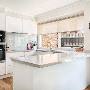 Design ideas for a mid-sized contemporary u-shaped kitchen pantry in Melbourne with a double-bowl sink, white cabinets, quartz benchtops, beige splashback, glass tile splashback, black appliances, vinyl floors, grey floor and beige benchtop.