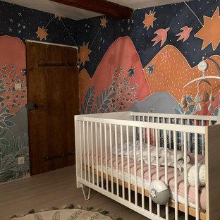 Cette photo montre une petit chambre de bébé neutre avec un mur multicolore, sol en stratifié, un sol beige, un plafond en poutres apparentes et du papier peint.